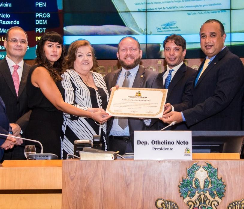 Cleide Coutinho recebe o diploma emoldurada por Rogperio Cafeteira, sua filha , Othelkino Neto, seu filho e Roberto Cista, aurtir da proposta
